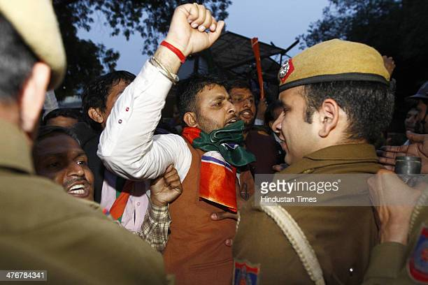Security personnel restraining BJP workers after the violent clash with AAP workers at BJP head office on Ashoka Road during AAP protest against...