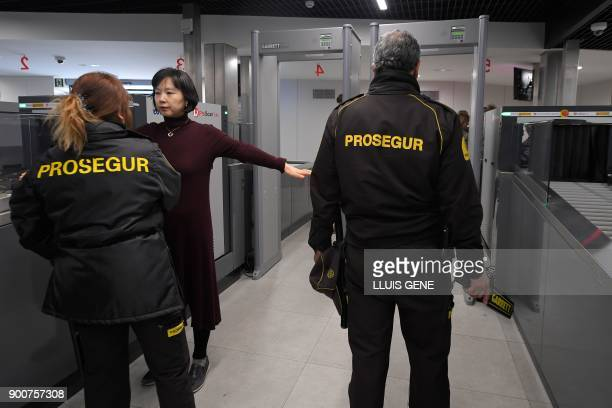 Security personnel search a woman with a metal detector before accessing the Sagrada Famila Basilica in Barcelona on January 3 2018 The Sagrada...