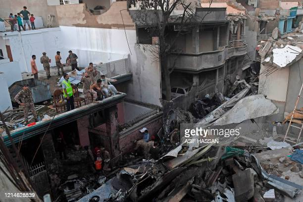 Security personnel search for victims in the wreckage of a Pakistan International Airlines aircraft after it crashed in a residential area in Karachi...