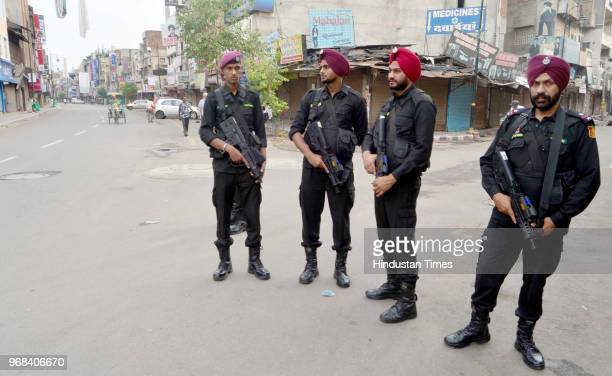 Security personnel stand alert outside closed shops at hall bazaar during a shutdown call given by radical Sikh organization 'Dal Khalsa' on the 34th...