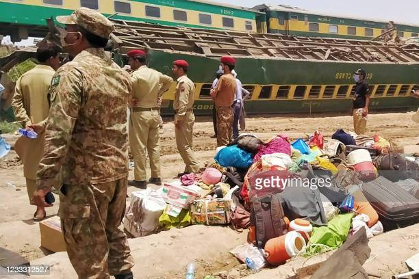 Security personnel stand at the site of a train accident in Daharki area of the northern Sindh province on June 7 as at least 34 people were killed...