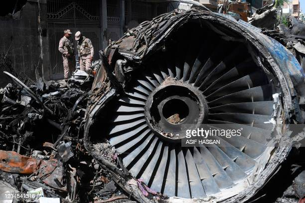 TOPSHOT Security personnel stand beside the wreckage of a plane at the site after a Pakistan International Airlines aircraft crashed in a residential...
