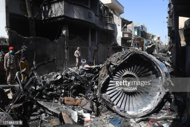 Security personnel stand beside the wreckage of a plane at the site after a Pakistan International Airlines aircraft crashed in a residential area...