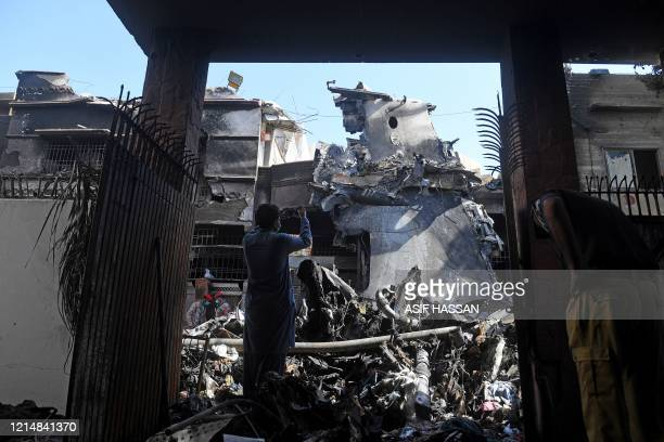 Security personnel stand gauard beside the wreckage of a plane as a man takes pictures at the site after a Pakistan International Airlines aircraft...