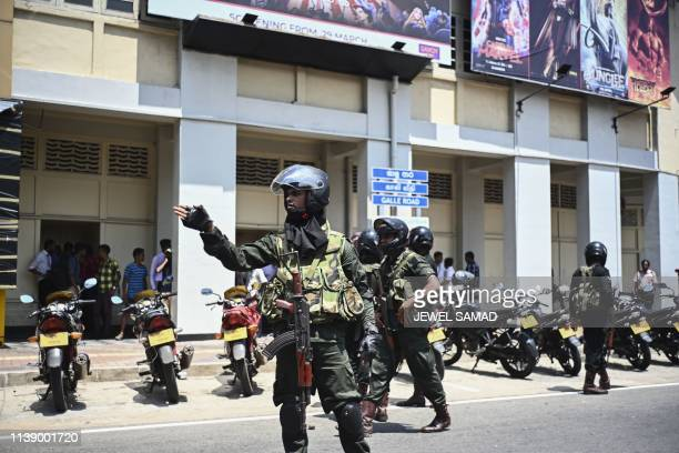 Security personnel stand guard after a controlled explosion in front of a movie theatre in Colombo on April 24 three days after a series of bomb...