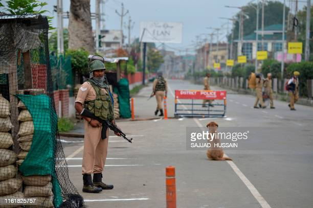 Security personnel stand guard at a check point on a deserted road during a lockdown in Srinagar on August 15 as India celebrates its 73rd...
