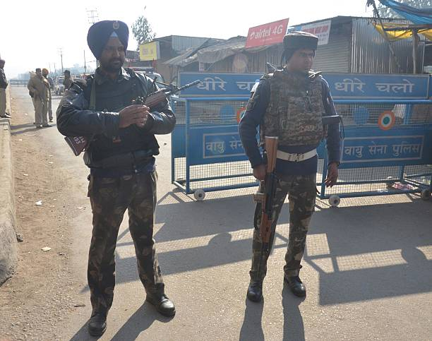 Security personnel stand guard at a road which leads to Air Force station at Dhaki Chowk after the fresh firing and alleged bomb explosion inside the.