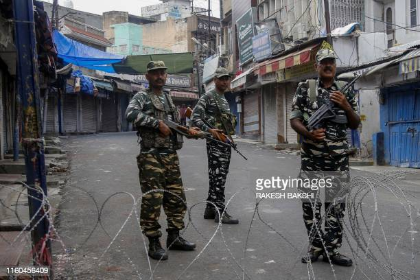 TOPSHOT Security personnel stand guard at a roadblock ahead of Muslim's Friday noon prayers in Jammu on August 9 after the Indian government stripped...