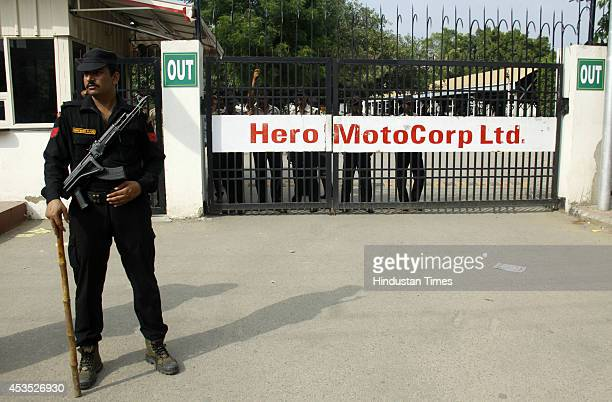 Security personnel stand guard at the gate of Hero MotoCorp company as hundreds of employees protest outside on August 12 2014 in Gurgaon India The...