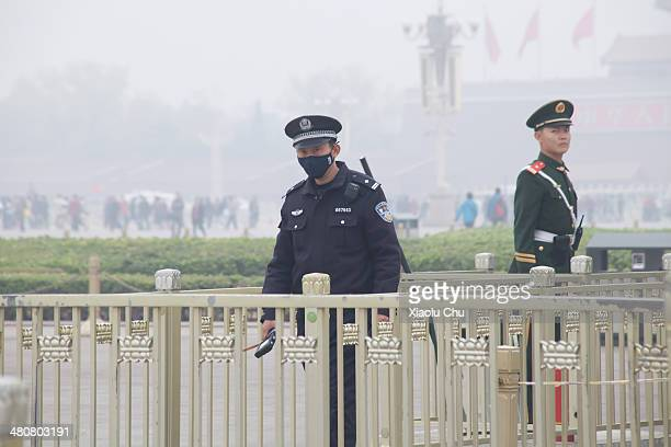 Security personnel stand guard at Tiananmen Square blanketed in smog on March 27 2014 in Beijing China An estimated 7 million people die worldwide...