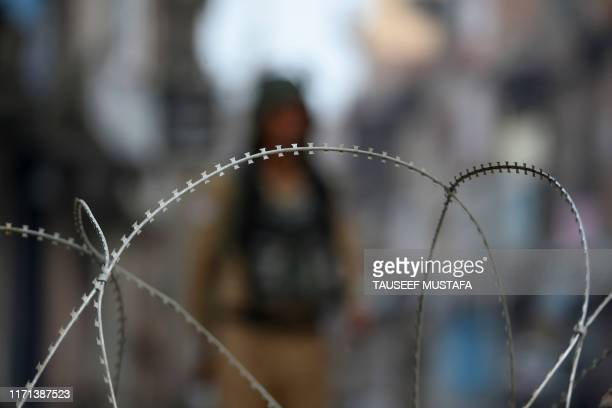 Security personnel stand guard behind unfold barbed wire during a lockdown at Maisuma locality of Srinagar on September 27 2019