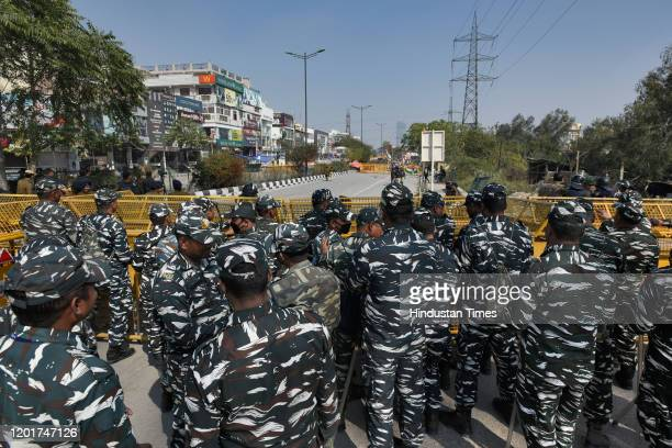 Security personnel stand guard in front of barricades as protesters prepare to march to Home Minister Amit Shah's residence, at Shaheen Bagh, on...
