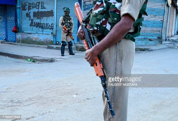 Security personnel stand guard in front of closed shops in Srinagar on August 23 2019 An Indian soldier was killed by Pakistani forces on the Kashmir...