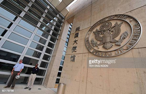 Security personnel stand guard in front the bullet proof glass wall of the new US embassy in Beijing on August 5, 2008. A massive new US embassy, the...