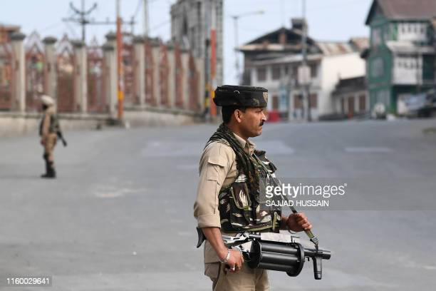 Security personnel stand guard on a street during a curfew in downtown Srinagar on August 6 2019 India's home affairs minister on August 6 hailed...