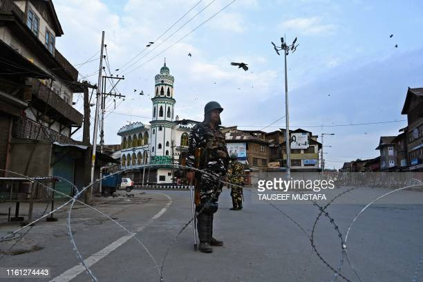 Security personnel stand guard on a street during a lockdown in Srinagar on August 12 2019 Indian troops clamped tight restrictions on mosques across...