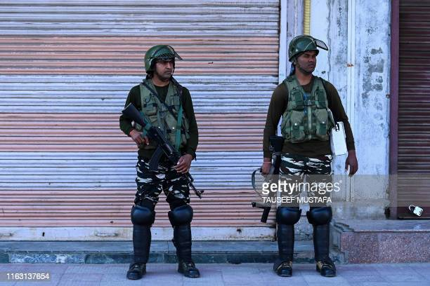 Security personnel stand guard on a street near closed shops in Srinagar on August 22 2019
