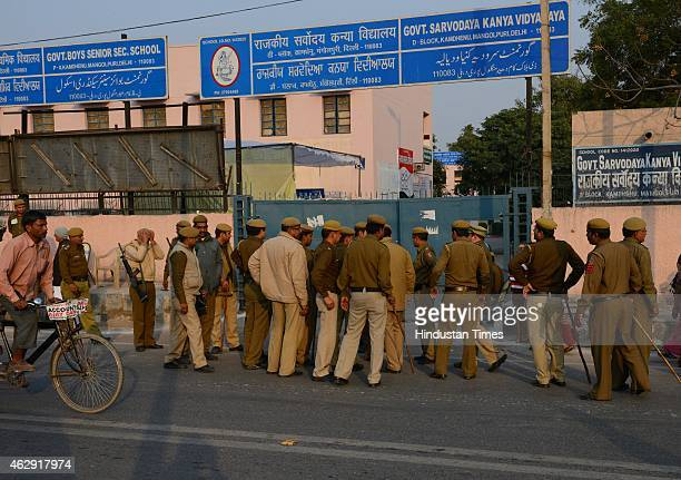 Security personnel stand guard outside at Mangol Puri polling station during the Delhi Assembly Elections 2015 on February 7 2015 in New Delhi India...