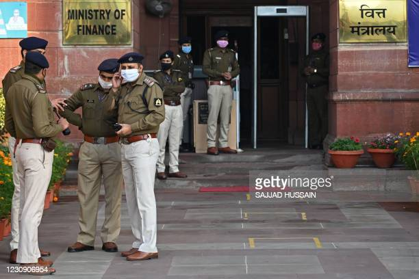 Security personnel stand guard outside the Finance Ministry as they wait for the arrival of India's Finance Minister Nirmala Sitharaman to leave for...