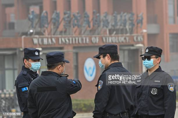 Security personnel stand guard outside the Wuhan Institute of Virology in Wuhan as members of the World Health Organization team investigating the...