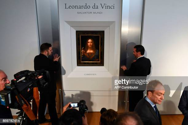Security personnel stand next to Leonardo da Vinci's Salvator Mundi after it was unveiled at Christie's in New York on October 10 2017 One of fewer...