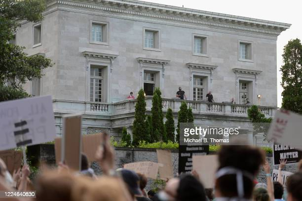 Security personnel stand on the balcony the home of Mark and Patricia McCloskey as protesters demonstrate against racism and police brutality outside...