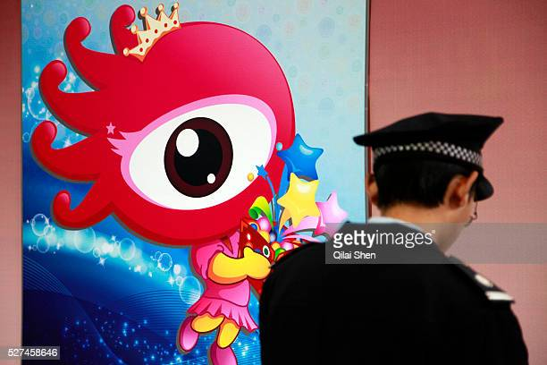 A security personnel stands beside a logo for Sinacom at the Spring Real Estate Fair in Shanghai China on 17 March 2012 Weibo Sina's popular...