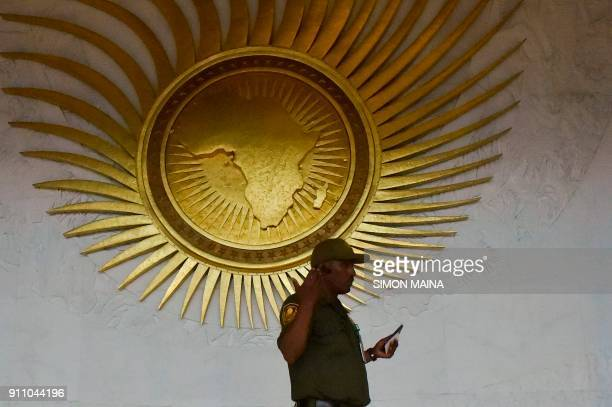 A security personnel stands by a sculpture representing the African continent before the start of the 30th Ordinary Session of the Assembly of Heads...