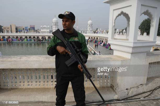 A security personnel stands guard as Sikh pilgrims take part in a religious ritual as they gather to celebrate the 550th birth anniversary of Guru...