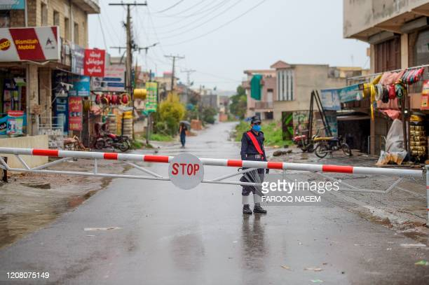Security personnel stands guard behind a barrier closing a street during a government-imposed lockdown as a preventive measure against the COVID-19...