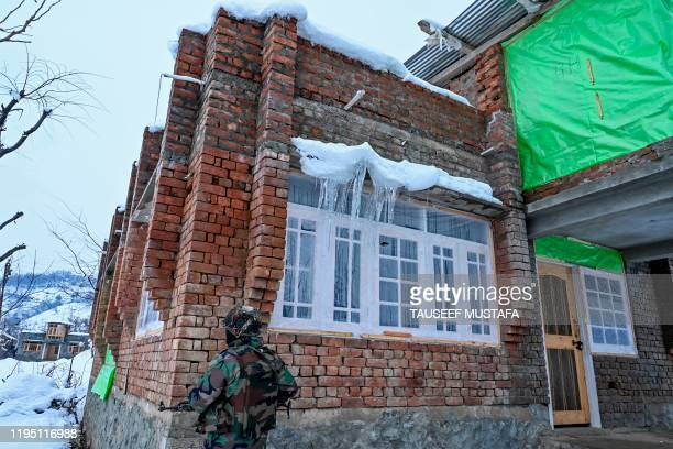 A security personnel stands guard near a site of a gunbattle between suspected militants and government forces at Khrew area of Pampore in Pulwama...