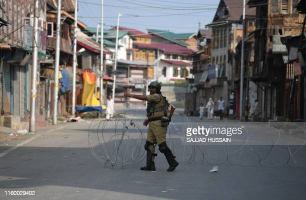 A security personnel stands guard on a street during a curfew in Srinagar on August 6 2019 India's home affairs minister on August 6 hailed historic...