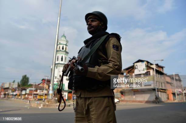 A security personnel stands guard on a street during a curfew in downtown Srinagar on August 6 2019 India's home affairs minister on August 6 hailed...