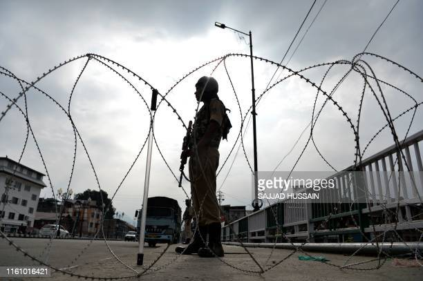 A security personnel stands guard on a street during a lockdown in Srinagar on August 11 after the Indian government stripped Jammu and Kashmir of...