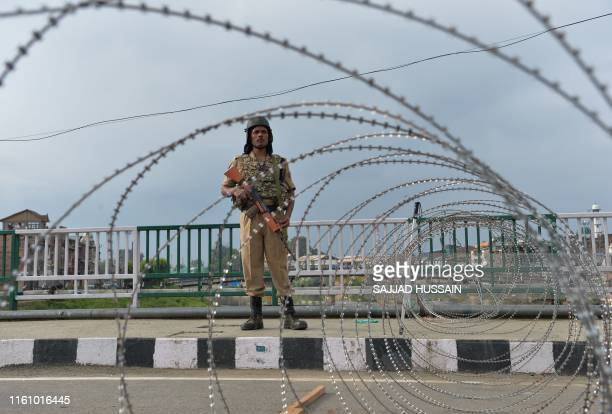 TOPSHOT A security personnel stands guard on a street during a lockdown in Srinagar on August 11 after the Indian government stripped Jammu and...