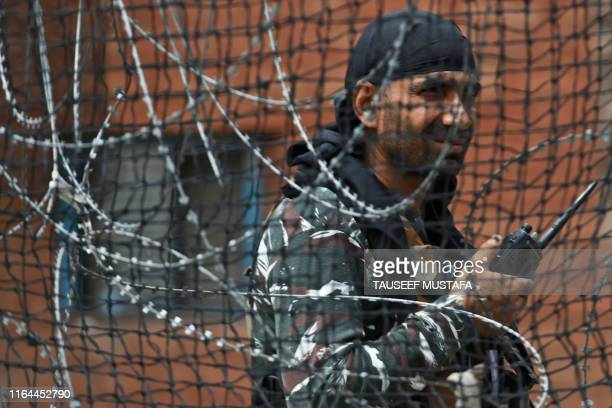 TOPSHOT A security personnel stands guard on a street in Srinagar on August 28 2019 The Himalayan valley is under a strict lockdown with movement...