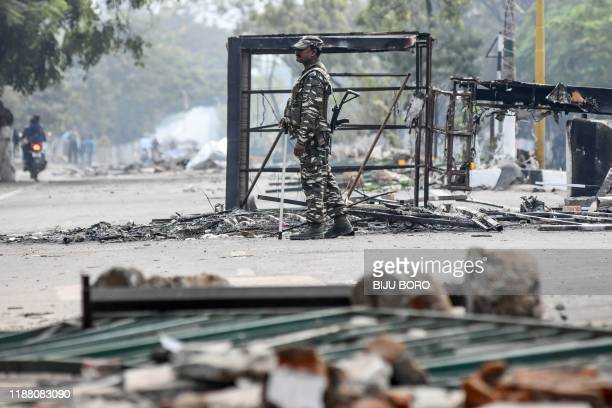 Security personnel stands near a traffic point destroyed earlier by demonstrators during a protest against the government's Citizenship Amendment...