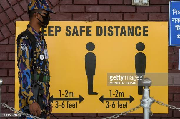 Security personnel stands next to a sign requesting to maintain social distancing as a preventive measure against the spread of the COVID-19...