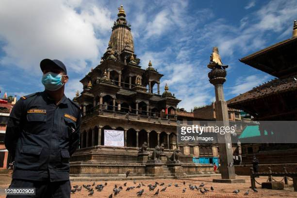 A security personnel stands on guard while wearing a face mask during the festival at the Krishna Mandir Krishna Janmashtami is an annual Hindu...