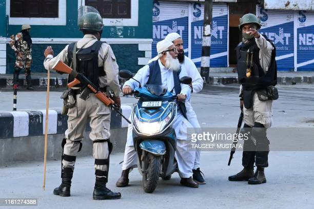 Security personnel stop Muslims for questioning during a lockdown in Srinagar on August 12 2019 Indian troops clamped tight restrictions on mosques...
