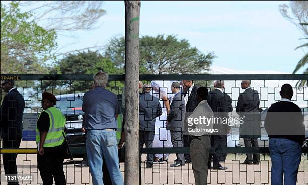 Security personnel surround the bride and her father as they arrive to attend the wedding celebrations for President Jacob Zuma's daughter Duduzile...