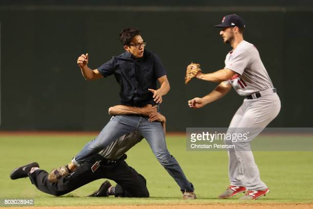 Security personnel tackle a fan as he runs onto the field and collides with infielder Paul DeJong of the St Louis Cardinals during the seventh inning...