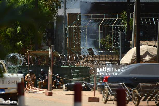 TOPSHOT Security personnel take cover as smoke billows from The Institute Francais in Ouagadougou on March 2 as the capital of Burkina Faso came...