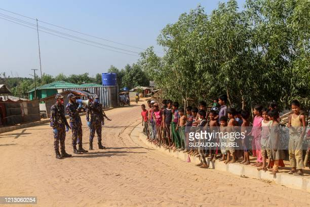 Security personnel use a loudspeaker to raise awareness about the COVID-19 coronavirus in a Rohingya refugee camp in Ukhia on May 15, 2020. -...