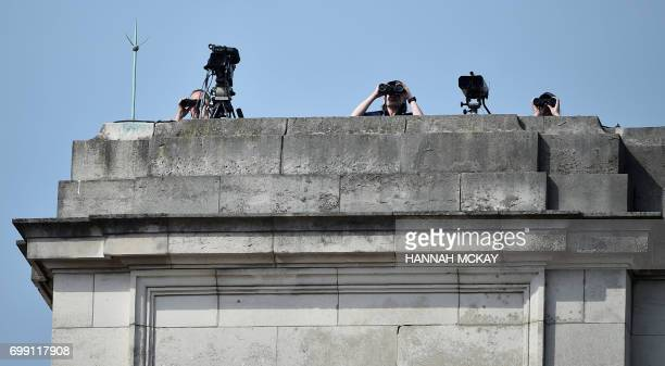Security personnel use binoculars from the rooftop of Buckingham Palace before the departure of Britain's Queen Elizabeth to the Houses of Parliament...