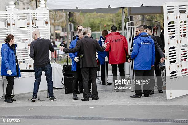 Security personnel use handheld scanning devices as attendees arrive at Porte de Versailles exhibition center for the second press day of the Paris...