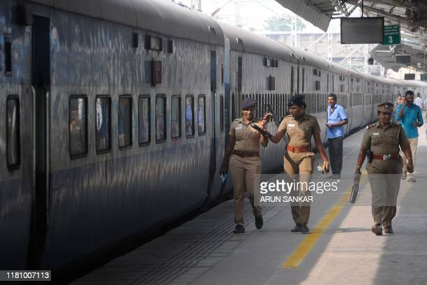 Security personnel walk beside a train at a railway station in Chennai on November 9 as security was tightened across India after a Supreme Court...