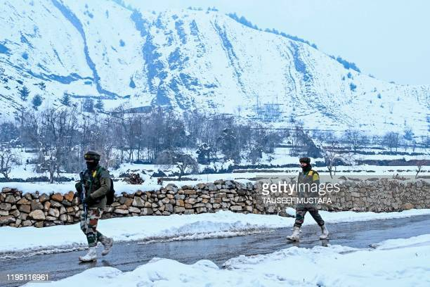 Security personnel walk on a road as they patrol near a site of a gunbattle between suspected militants and government forces at Khrew area of...