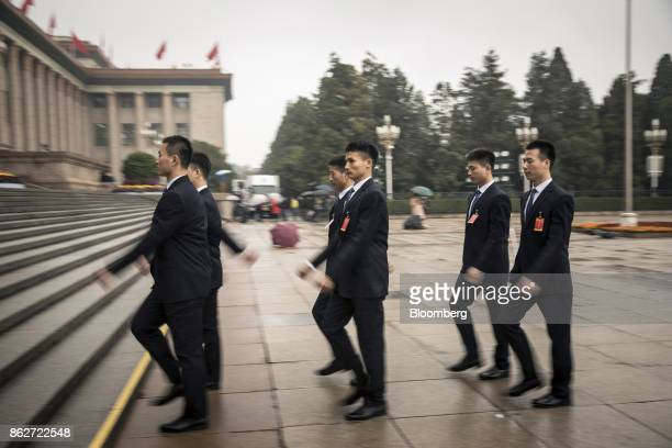 Security personnel walk towards the Great Hall of the People after the opening ceremony of the 19th National Congress of the Communist Party of China...