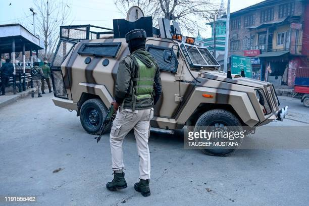 A security personnel walks past a security vehicle as he stands guard on a street after a grenade blast in Srinagar on January 4 2020